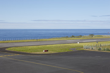 Airport runway close to the ocean with lines and fence