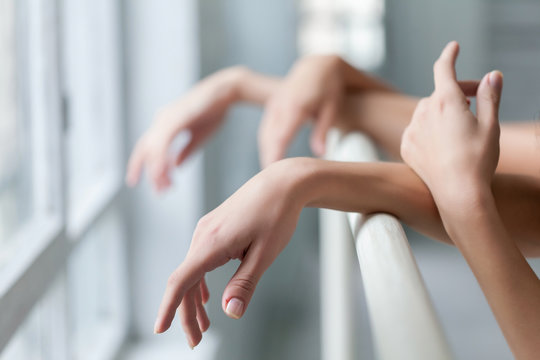The  hands of two classic ballet dancers at barre