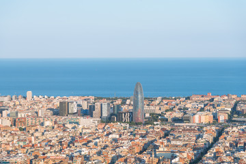 The Torre Agbar in the Poblenou district of Barcelona. The Tower is surrounded by other skyscrapers. The Torre Agbar is intended to recall the shape of a geyser rising into the air