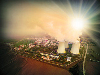 Aerial view to nuclear power plant in industrial landscape. Radiation and air pollution theme. Warm filtered picture.