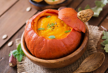 Pumpkin cream soup with peppers and herbs in a pumpkin