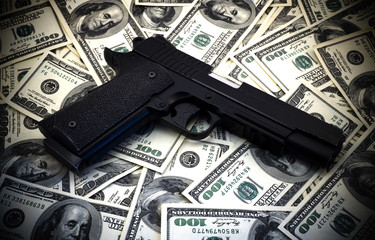 Black and chrome gun pistol and money dollars background high contrasted with vignetting effect