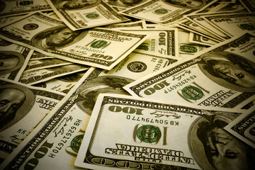 Mount of hundred dollar banknotes background texture warm filtered high contrasted with vignetting effect