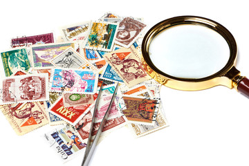 Old used postage stamps and magnifier