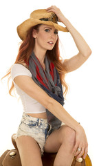 cowgirl with red hair sit on saddle touch hat