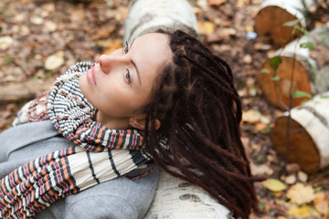 Girl with dreadlocks sits near birch logs