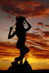 silhouette cowgirl one foot on saddle
