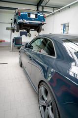 KFZ-Werkstatt von innen mit einem Auto auf einer Hebebühne
