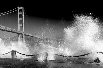 Golden Gate Bridge. Wild huge waves crashing. Dramatic black and white image of stormy night.