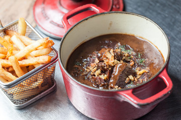 Belgian beef stew 'carbonades flamandes' in a vintage pot with French fries
