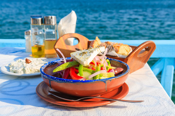 Greek salad on table in Greek tavern with blue sea water in background, Samos island, Greece