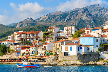 Typical Greek fishing boat in Kokkari bay with town houses in background, Samos island, Greece