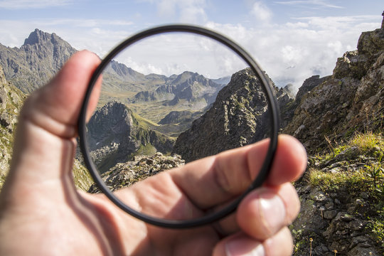 Hand puts a transparent clean protective UV filter to the camera, in the background a beautiful landscape and mountains