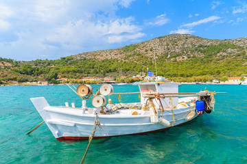 White traditional fishing boat on sea water in Posidonio bay, Samos island, Greece