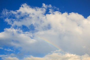 rainbow in the blue sky after the rain with lighting flare