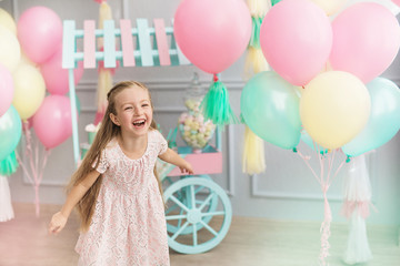Little girl laughs in a studio decorated many balloons
