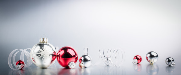 Wall Mural - Christmas balls with ribbon on snow