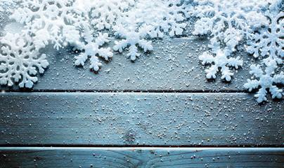 Snowflakes border on grunge wooden background.