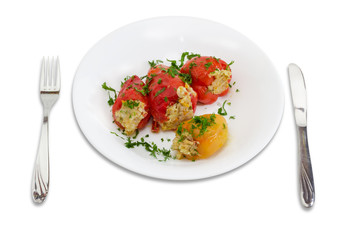 Stuffed bell peppers on a white dish, fork and knife