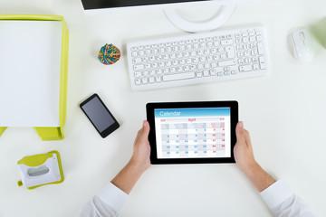 Businessperson With Digital Tablet Showing Calendar