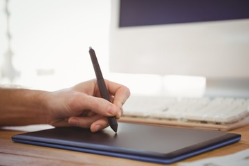 Cropped hand of man working on graphics tablet