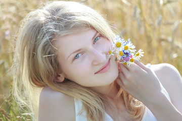 Summer outdoor head and shoulders portrait of blonde girl at