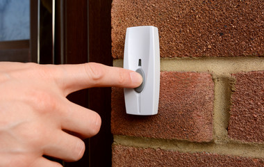 Close-up of woman pressing a doorbell