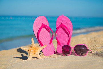 The sea, beach, sand and women's accessories: pink flip-flops, sunglasses and starfish