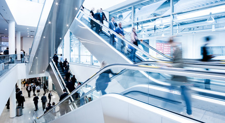 Blurred people using a skywalk/staircase