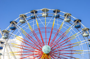 Ferris wheel on white on blue skype and cloud.