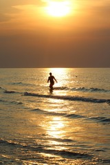 A girl comes out of the sea at sunrise