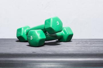 Green dumbbells on a step deck. Three kilograms.