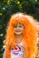 Little girls in brightly colored carnival wigs in the setting su