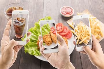 riends using smartphones to take photos of fried chicken and fre