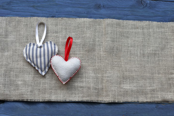 Hearts on burlap and blue wooden background
