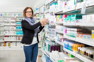 Smiling Female Customer Choosing Product At Pharmacy