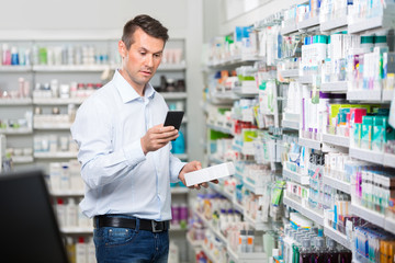 Customer Checking Information On Mobile Phone In Pharmacy