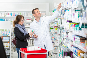 Chemist In Labcoat Removing Medicine For Female Customer