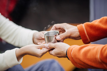 Womans and mens hands holding hot cup of tea in forest camp