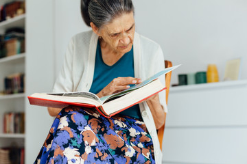 Old woman sitting and reading book