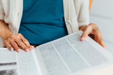 Closeup of old woman rading book