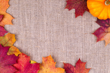 Background from autumn leaves and pumpkin on burlap