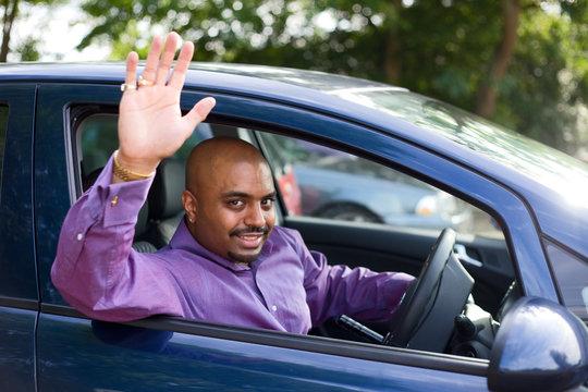 man waving goodbye from his car