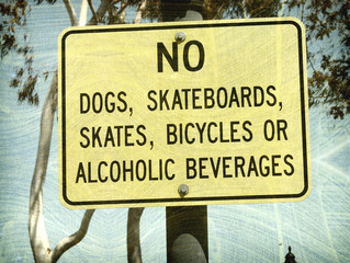 aged and worn vintage photo of no skateboards or dogs sign