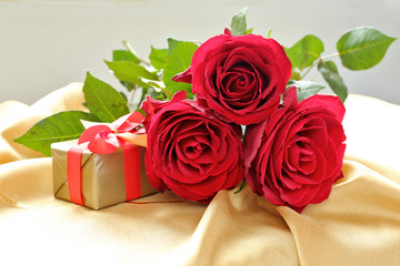 Roses  with gift box on gold tablecloth.