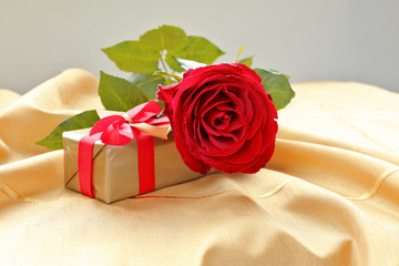 Rose with gift box on gold tablecloth.