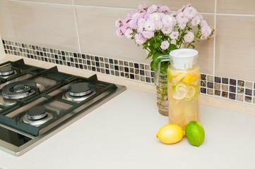Modern kitchen, clean interior design, lemonade drink and flowers