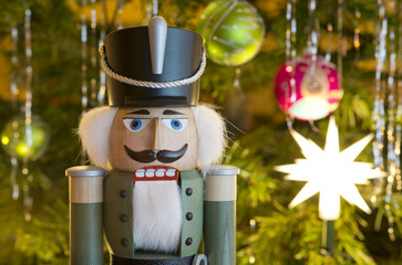 Toy soldier wooden nutcracker statue standing in front of decorated Christmas tree