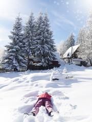 Girl Making a snow angel. Fantastic winter wonderland