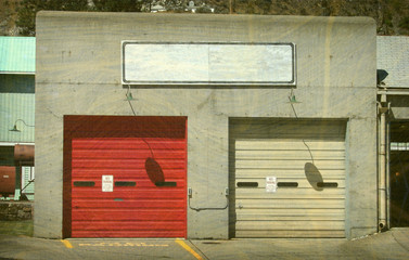 aged and worn vintage photo of concrete garage with metal doors